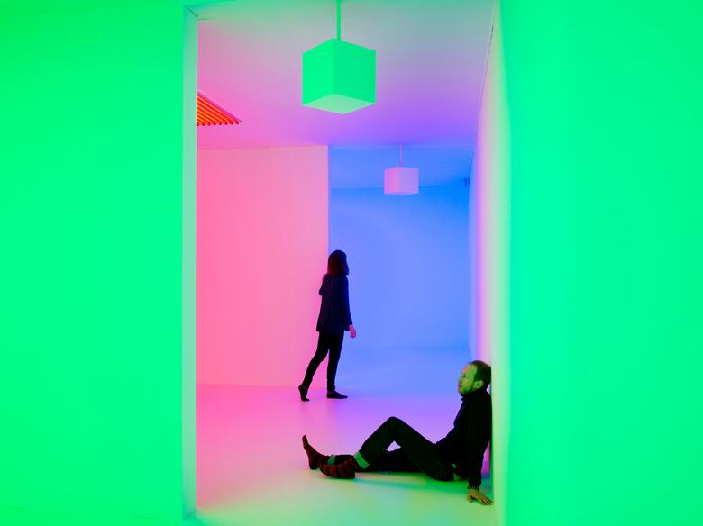 Visitors sitting and standing in Green and Pink Light Installation by artist, Carlos Cruz-Diez at Hayward Gallery