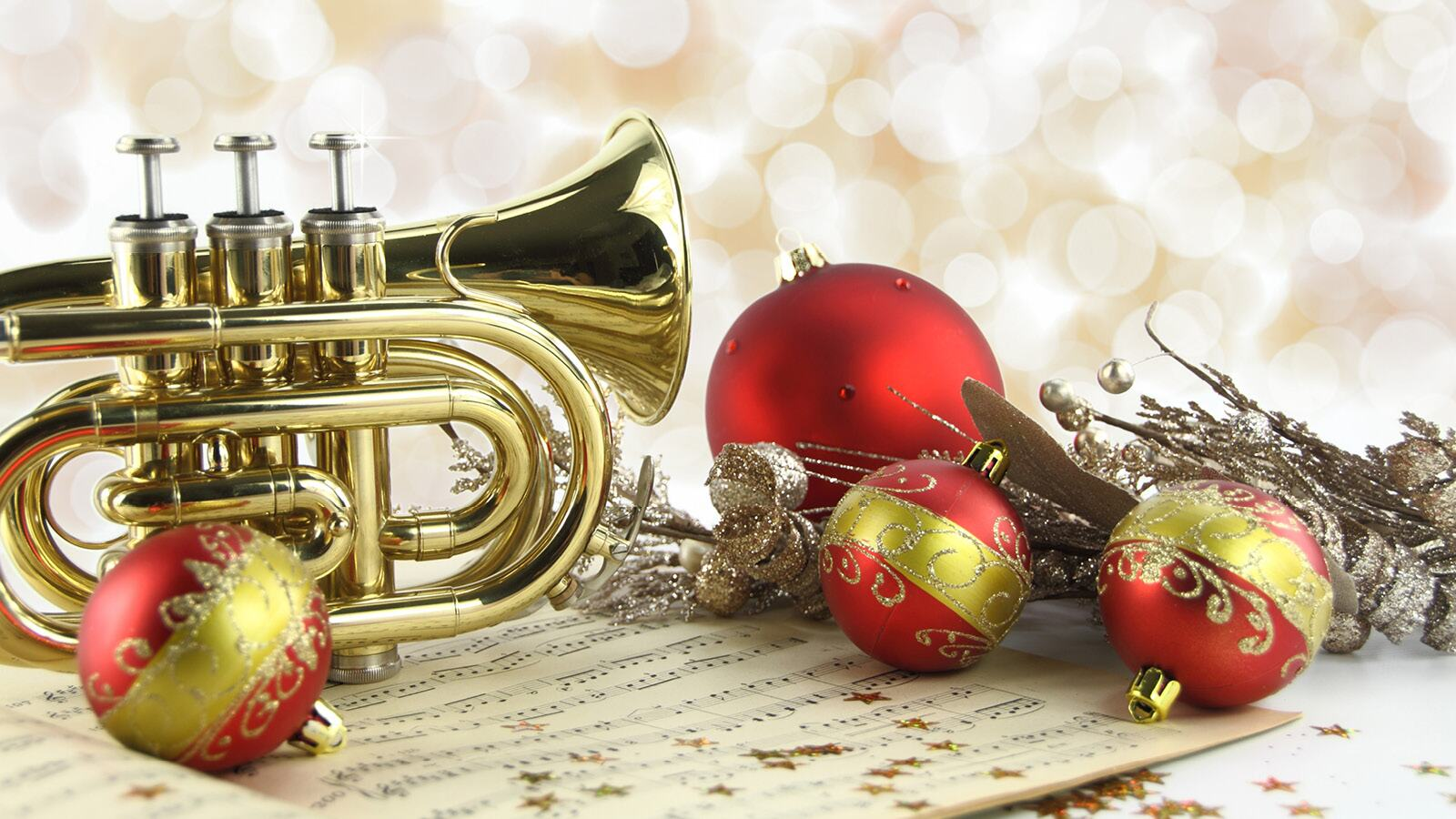 A trumpet and red baubles on top of sheet music