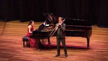 A pianist and trombonist performing on stage