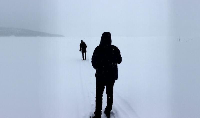 Two people walking in snow