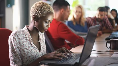 Closeup side view of group of software developers working late at IT office. There is African american woman with short blond hair in focus, her colleagues in background, blurry.