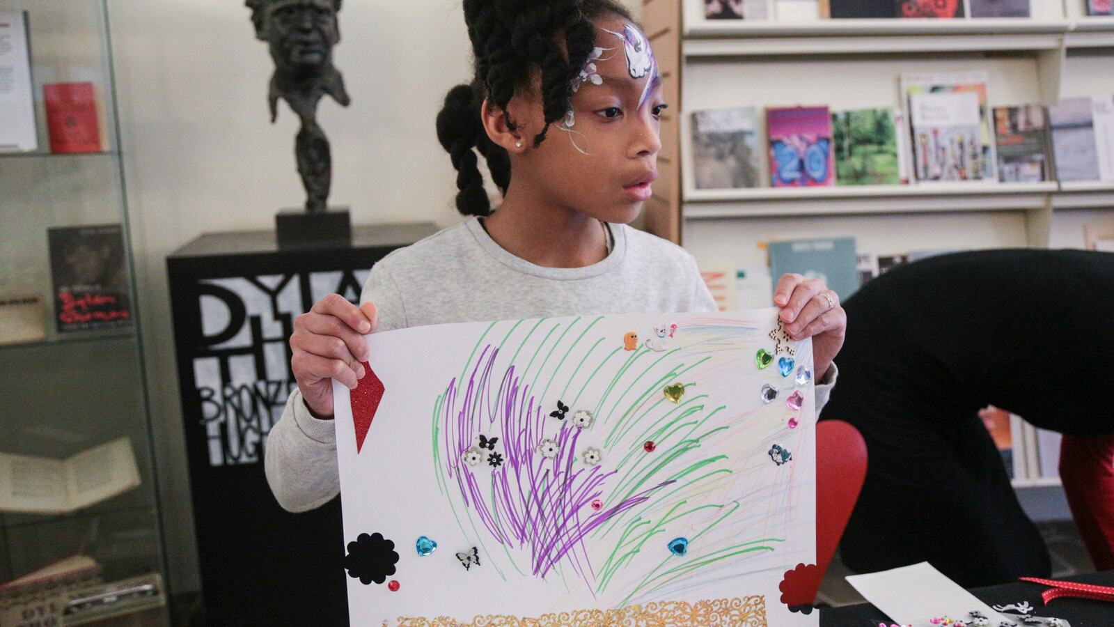 Photo of a girl holding up a drawing she has done at a Southbank Centre poetry workshop
