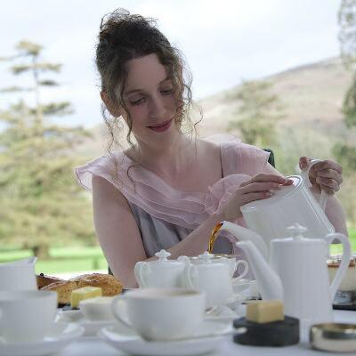 Seren Charrington-Hollins pours tea at a breakfast table