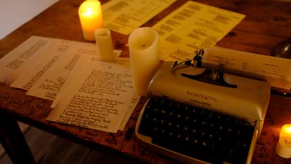 Constructing Spaces, image of typewriter and lit candles on a desk