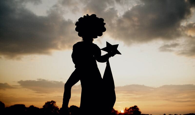 Silhouette of a drag queen under a sunset