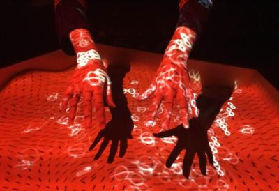 Hands underneath a red light projector showing images of symbols