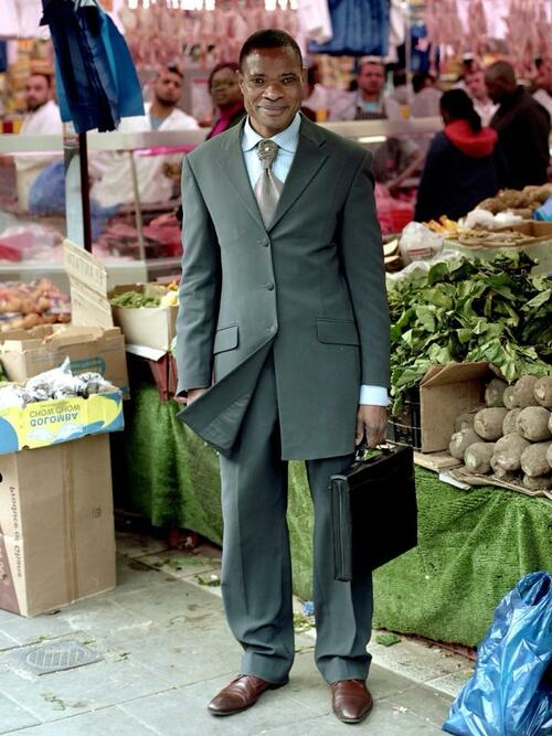 Photograph submitted by Errin Yesilkaya for the 'Inspired by Arbus' photography competition run by Southbank Centre with UAL. Photograph depicts a smartly dressed man standing outside a shop in Peckham, South London