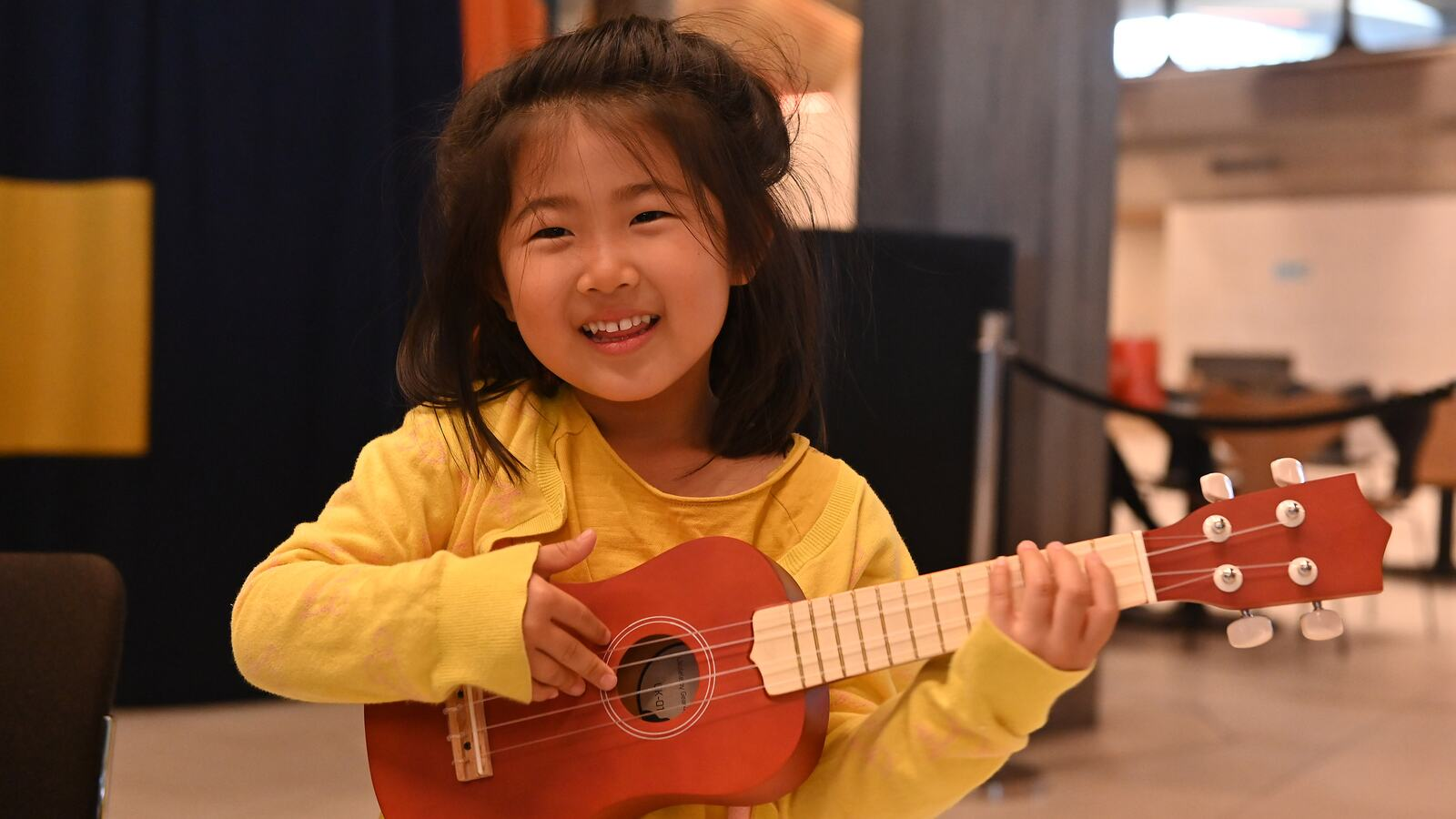 Child playing the ukulele in Queen Elizabeth Hall Foyer