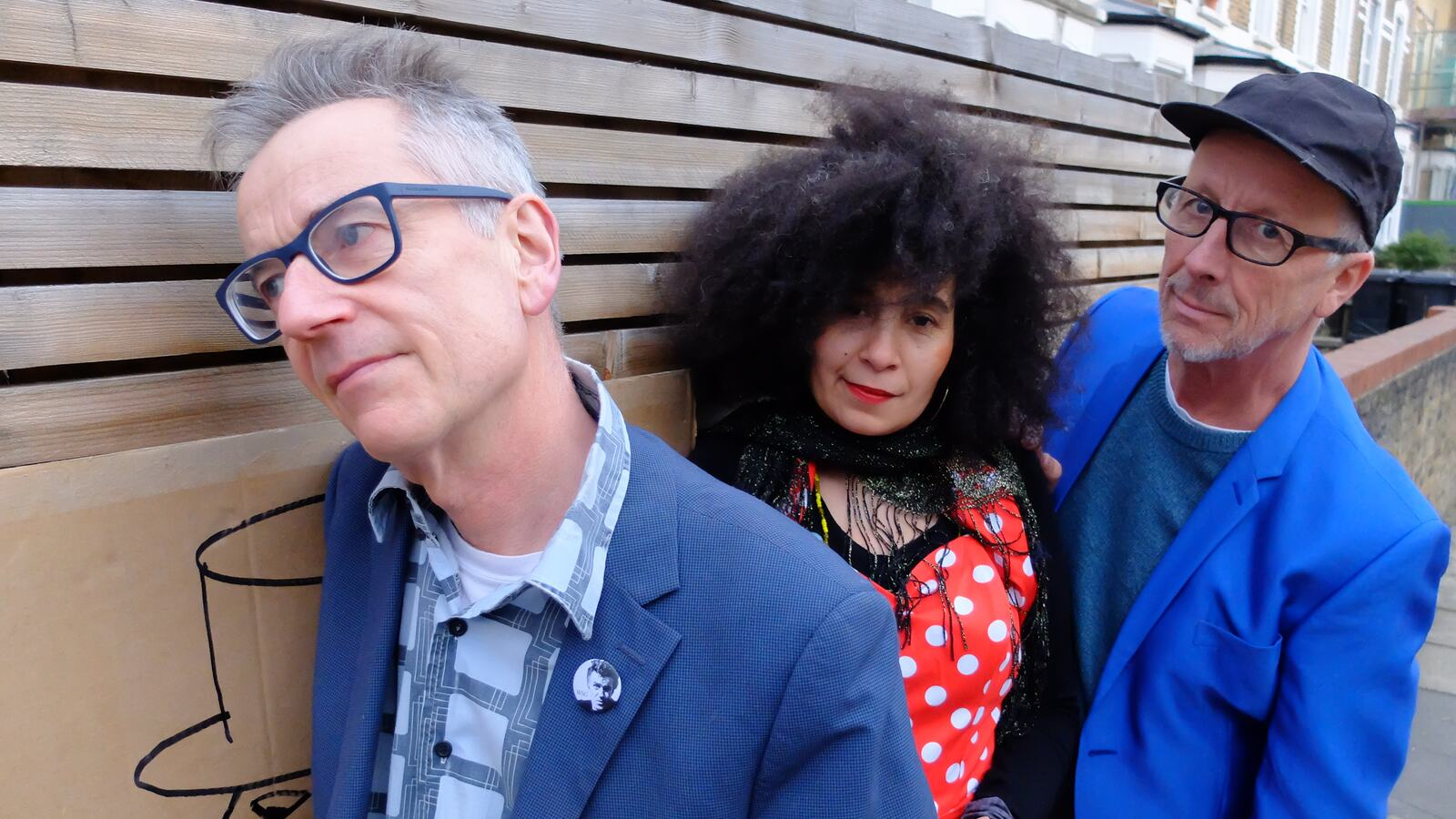 John Hegley, Cina Aissa and Mike Tomes leaning against a wall
