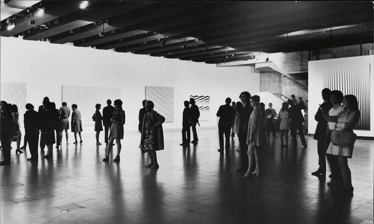 Visitors the Hayward Gallery's 1971 exhibition of the works of Bridget Riley take in the art work.