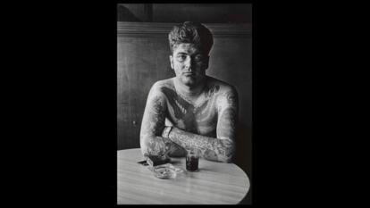 Jack Dracula at a bar, New London, Conn. The 1961 photograph by Diane Arbus depicting a topless tattooed man seated in a bar
